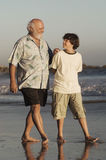 Grootvader en Kleinzoon die op Strand lopen Royalty-vrije Stock Foto