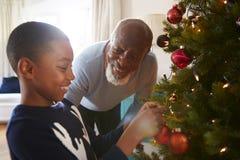 Grootvader en Kleinzoon Hangende Decoratie op Kerstboom thuis samen stock fotografie