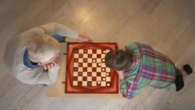 Grootvader en kleinzoonspelenschaak Het bejaarde onderwijst schaak om een jong vet kind te spelen Huiscomfort, familieidylle stock videobeelden