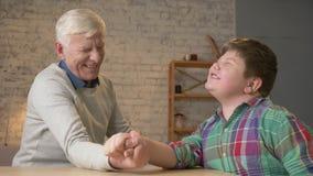 Grootvader en kleinzoonwapenworsteling in een comfortabele ruimte thuis Het meten van krachten in wapen het worstelen Jong vet ge stock video