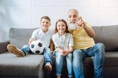Grootvader en zijn kleinkinderen die op hoogtepunten van voetbalspel letten royalty-vrije stock afbeelding