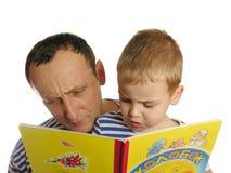 Grootvader gelezen boek met kleinzoon stock afbeelding