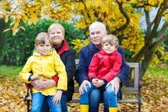 Grootvader, grootmoeder en twee kleine jong geitjejongens, kleinkinderen die in de herfstpark zitten stock foto's