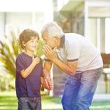 Grootvader het fluisteren geheim in oor van kleinzoon royalty-vrije stock afbeelding