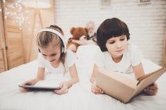 Grootvader, kleinzoon en kleindochter thuis De kinderen luisteren aan muziek en lezen terwijl de opa slaapt royalty-vrije stock afbeeldingen