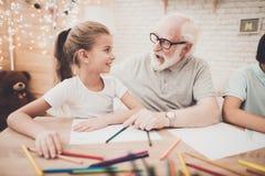 Grootvader, kleinzoon en kleindochter thuis De opa helpt kinderen trekken royalty-vrije stock afbeeldingen