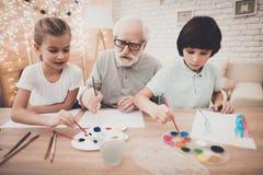 Grootvader, kleinzoon en kleindochter thuis De opa helpt kinderenverf stock foto