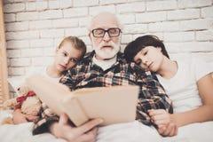Grootvader, kleinzoon en kleindochter thuis De opa en de kinderen lezen boek royalty-vrije stock afbeeldingen