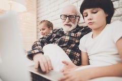 Grootvader, kleinzoon en kleindochter thuis De opa en de kinderen lezen boek en gebruiken laptop stock fotografie