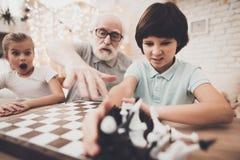 Grootvader, kleinzoon en kleindochter thuis De opa onderwijst kinderen hoe te om schaak te spelen stock afbeelding