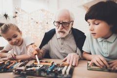 Grootvader, kleinzoon en kleindochter thuis De opa onderwijst kinderen hoe te solderen royalty-vrije stock afbeeldingen