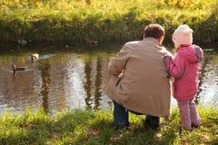 Grootvader met kleindochter in hout in de herfst l Stock Foto's