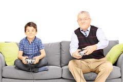 Grootvader met zijn neef gezet op een moderne bank die vide spelen royalty-vrije stock afbeeldingen