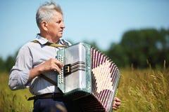 Grootvader in overhemdsspel op harmonika stock foto's