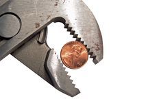 Groove Lock Pliers and a US Penny. Groove lock pliers griping or squeezing a United States penny royalty free stock images