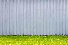 Grooved metal wall. Light blue industrial grooved metal wall and some green grass Stock Photography