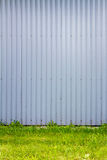 Grooved metal wall. Light blue industrial grooved metal wall and some green grass Stock Photos