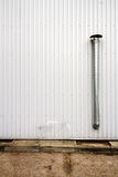 Grooved metal wall. White industrial grooved metal wall with metal chimney Royalty Free Stock Image