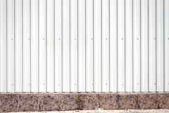 Grooved metal wall. White industrial grooved metal wall with stone tile basement Royalty Free Stock Photo