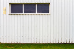 Grooved metal wall with a window. White industrial grooved metal wall with a window and some green grass Royalty Free Stock Image