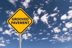 Grooved pavement road sign. Against blue cloudy sky royalty free stock images