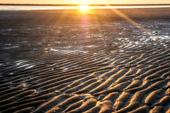 Grooves on the beach. Furrows in the beach with a sunset in the background Royalty Free Stock Photo