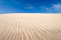 Grooves on dune. Dune with natural grooves and blue sky Stock Images