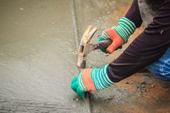 Grooving on concrete pavement by worker used deformed steel bar Stock Image