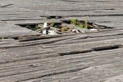 Gropen (hål) i det gamla och slitna golvet Den materiella beläggningen Royaltyfri Bild
