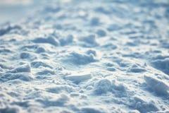 Gropig yttersida av spruckna ljus och skuggor för textur för kontrast för isskorpahöjd på snöfält arkivbild