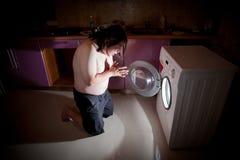 Gros agenouillement asiatique d'homme dans la prière par la machine à laver Photographie stock libre de droits