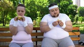 Gros couples mangeant des hamburgers, se sentant coupables pour arrêter le régime, aliments de préparation rapide adonnés photos libres de droits