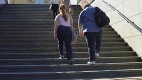 Gros couples marchant ensemble sur les escaliers, problèmes du poids excessif parmi les jeunes banque de vidéos