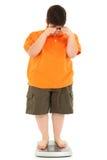 Gros enfant morbide obèse sur l'échelle Photo stock