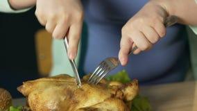 Gros femelle coupant rudement le poulet rôti avec l'argenterie, nutrition malsaine clips vidéos