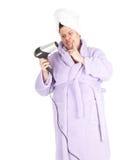 Gros femme dans le peignoir gardant le cheveu-dessiccateur Photographie stock libre de droits