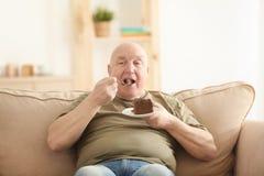 Gros gâteau mangeur d'hommes supérieur tout en se reposant sur le sofa à la maison Image libre de droits