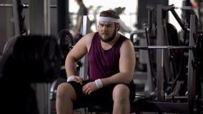 Gros homme contrarié pensant au-dessus des problèmes de poids, désir de perdre le poids, séance d'entraînement de gymnase photos libres de droits