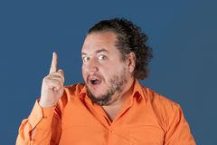 Gros homme dans la chemise orange tenant son pouce  Il a eu une grande idée photos libres de droits