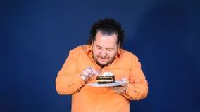 Gros homme drôle dans la chemise orange avec un morceau de gâteau de chocolat d'un plat banque de vidéos
