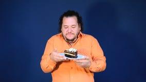 Gros homme drôle dans la chemise orange avec un morceau de gâteau de chocolat d'un plat clips vidéos