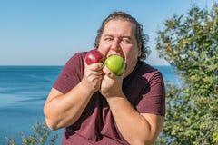 Gros homme drôle sur l'océan mangeant des fruits Vacances, perte de poids et consommation saine photo libre de droits