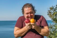 Gros homme drôle sur l'océan mangeant des fruits Vacances, perte de poids et consommation saine photos stock