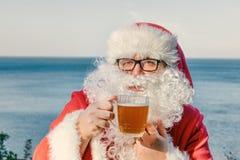 Gros homme en verres habillés comme bière potable de Santa sur l'océan Drôle, bu et heureux photo stock