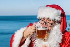 Gros homme en verres habillés comme bière potable de Santa sur l'océan Drôle, bu et heureux photographie stock libre de droits