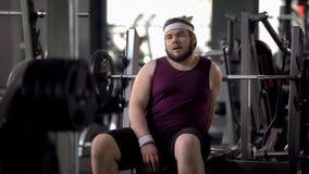 Gros homme fatigué ayant le repos après l'exercice de séance d'entraînement, force des muscles, s'exerçant images libres de droits