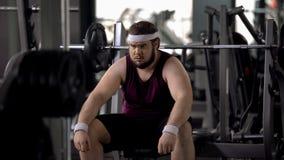 Gros homme fatigué pensant au-dessus des problèmes de poids, désir de perdre le poids, séance d'entraînement de gymnase photo stock