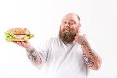 Gros homme heureux montrant le grand hamburger Photographie stock