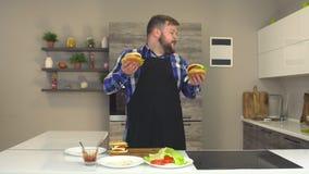 Gros homme satisfait avec une danse de barbe et de tablier et le sourire dans la cuisine avec des hamburgers clips vidéos