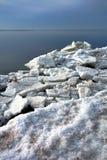 Gros morceaux de flotteur de glace et morceaux gelés sur le rivage d'hiver Image libre de droits